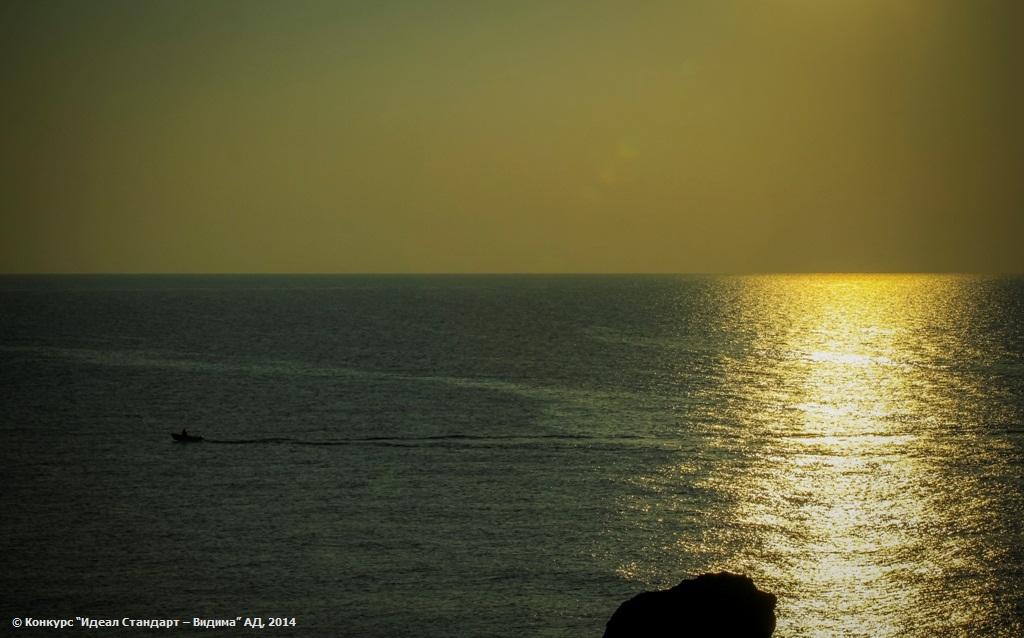 Рибарят и морето по изгрев слънце